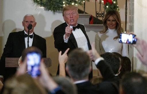 President Donald Trump, joined by Vice President Mike Pence, left, and first lady Melania Trump, right, acknowledges the crowd during the Congressional Ball in the Grand Foyer of the White House in Washington, Saturday, Dec. 15, 2018.