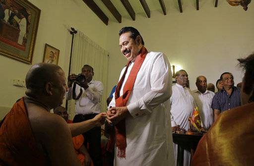 Sri Lanka's disputed Prime Minister Mahinda Rajapaksa speaks with a Buddhist monk after signing his resignation letter at his residence in Colombo, Sri Lanka, Saturday, Dec. 15, 2018. Rajapaksa resigned on Saturday, saying he wants to end a political impasse over his appointment. (AP Photo/Eranga Jayawardena)
