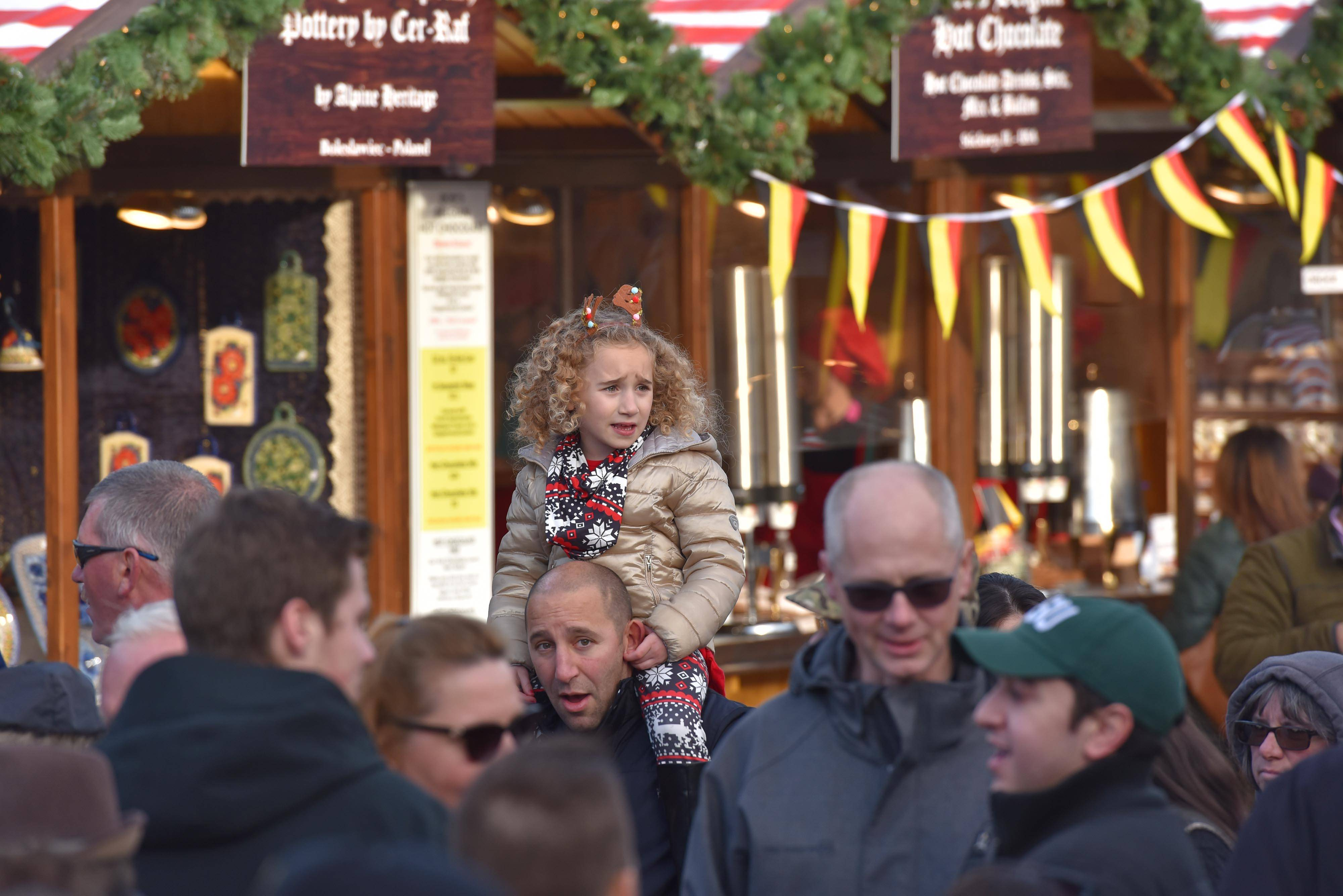 A young girl gets a better view of all the holiday happenings Sunday at the Naper Settlement's Christkindlmarket in Naperville. The market will be open Monday through Friday and again on Christmas Eve.
