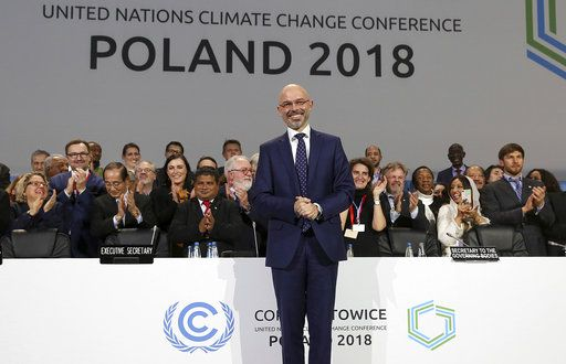 President Michal Kurtyka poses for a photo after adopting the final agreement during a closing session of the COP24 U.N. Climate Change Conference 2018 in Katowice, Poland, Saturday, Dec. 15, 2018.