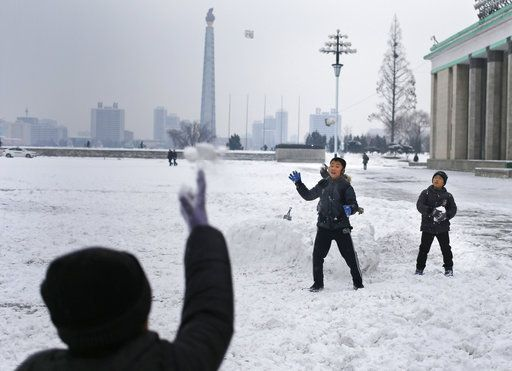 North Korean boys play snowball fight on Kim Il Sung Square as the Tower of The Juche Idea is seen in the background in Pyongyang, North Korea, where the winter season has started, on Sunday, Dec. 16, 2018.