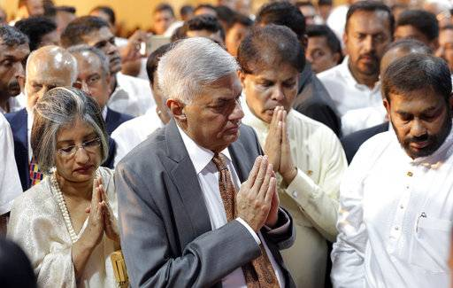 Sri Lanka's reinstated prime minister Ranil Wickeremesinghe, center, greets to Buddhist monks with his wife Maithree, left, after assuming duties in Colombo, Sri Lanka, Sunday, Dec. 16, 2018. Sri Lanka's president has reappointed Ranil Wickremesinghe as prime minister, nearly two months after firing him and setting off weeks of political stalemate.