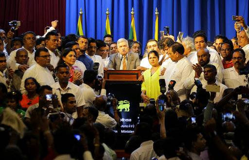 Sri Lanka's reinstated Prime Minister Ranil Wickeremesinghe, center, surrounded by his loyal lawmakers and supporters speaks after assuming duties in Colombo, Sri Lanka, Sunday, Dec. 16, 2018. Sri Lanka's president has reappointed Ranil Wickremesinghe as prime minister, nearly two months after firing him and setting off weeks of political stalemate.