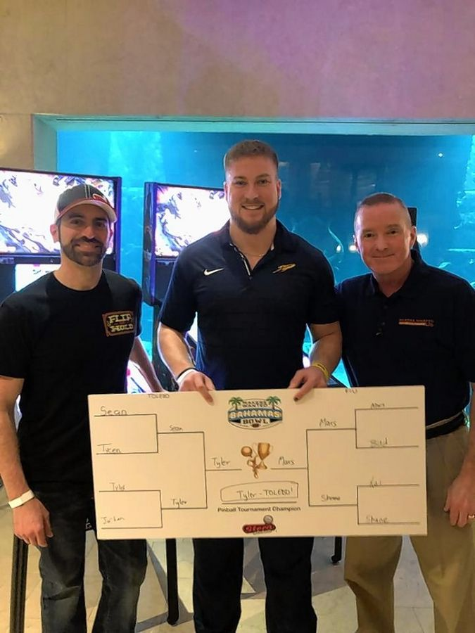 Zach Sharpe, Stern Pinball's director of marketing, left, and Elk Grove Village Mayor Craig Johnson, right, congratulate Toledo linebacker Tyler Taafe on winning a pinball tournament, ahead of the Elk Grove-sponsored Makers Wanted Bahamas Bowl.