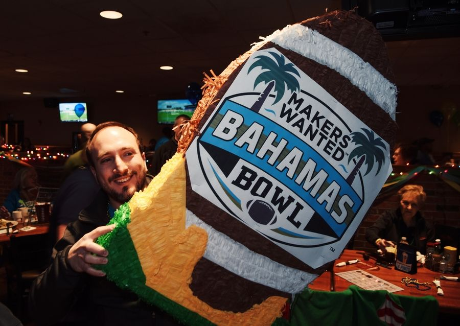 Giordan Kaplan carries the promotional logo during Friday's viewing party for the Makers Wanted Bahamas Bowl at Real Time Sports. Elk Grove Village paid $300,000 to sponsor the bowl game.
