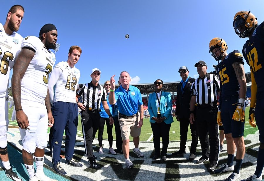 Elk Grove Village Mayor Craig Johnson flips the coin prior to the start of the 2018 Makers Wanted Bahamas Bowl at Thomas A. Robinson National Stadium in Nassau, Bahamas on Friday, Dec. 21.