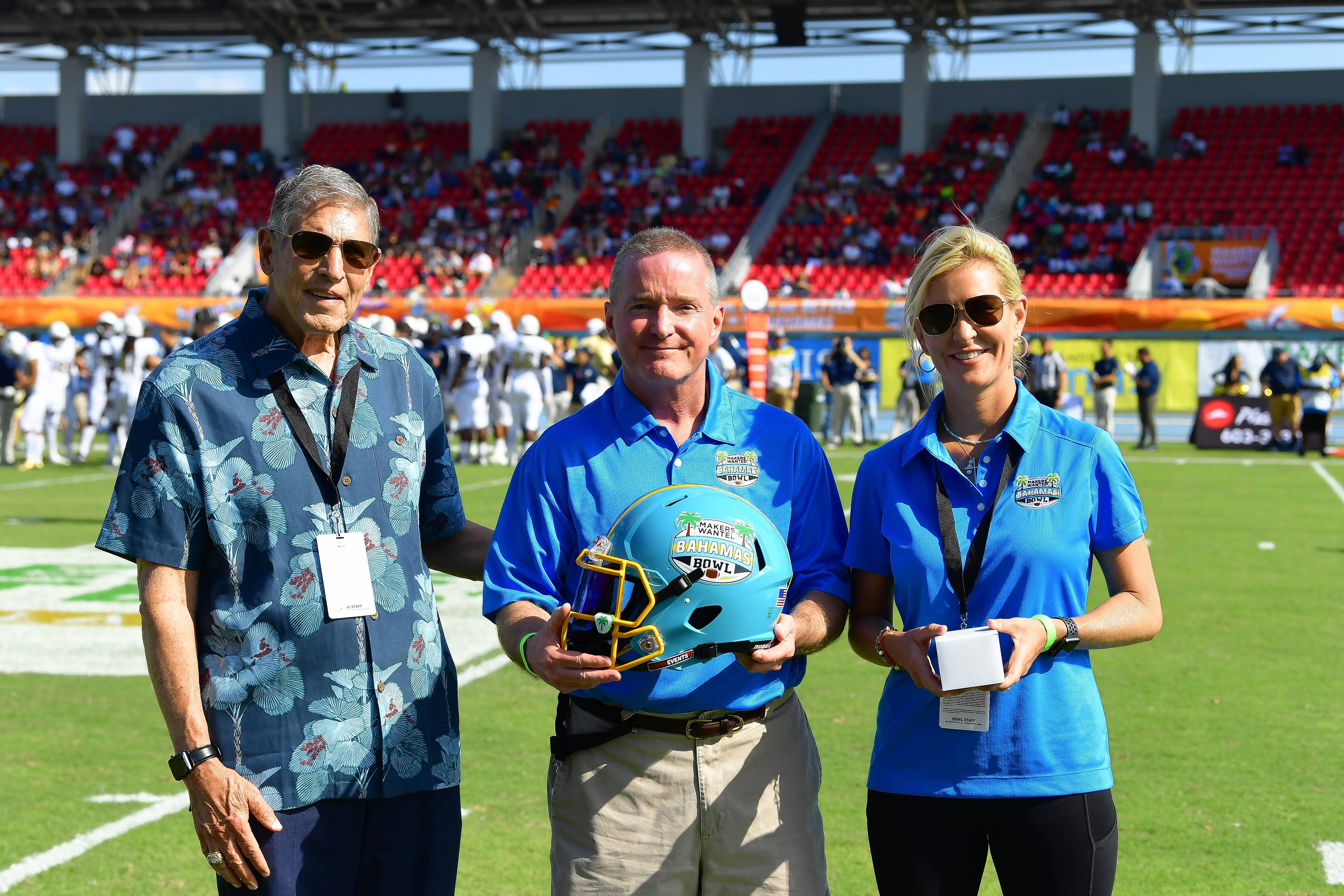 Makers Wanted Bahamas Bowl executives Richard Giannini, left, and Lea Miller-Tooley flank Elk Grove Village Mayor Craig Johnson during an on-field presentation in the first quarter of the 2018 Makers Wanted Bahamas Bowl at Thomas A. Robinson National Stadium in Nassau, Bahamas.