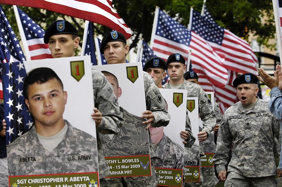 The portraits of Delta Company, 1st Battalion, 178th Infantry soldiers killed in Afghanistan are carried into the Woodstock Square as the unit returns from a year away.