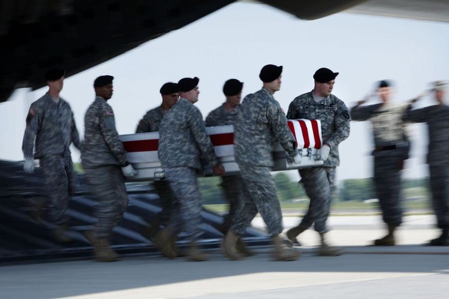 A team carries the transfer case containing the remains of Delta Company Spc. Lukasz D. Saczek of Lake in the Hills at Dover Air Force Base, Delaware, in May 2009.
