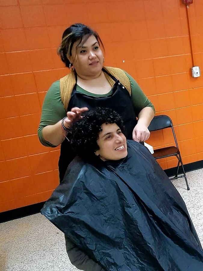 Lucy Izaguirre of Joliet, top, one of Saturday's volunteers, discusses a hairstyle with Mirna Gutierres of Mexico before giving a complimentary cut.