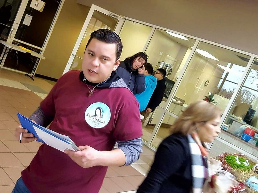 Edwin Hernandez, head of Caridades de la Cruz (Charities of the Cross), organizes volunteers at Saturday's fifth annual homeless fair, where an estimated 125 people received food, clothing, showers and haircuts.