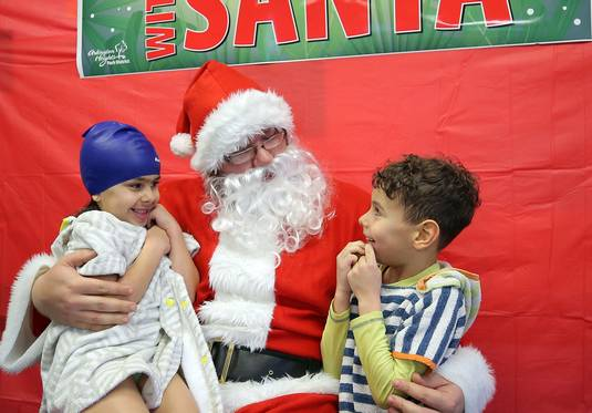 Leona Rodriguez, 5, of Arlington Heights and her 7-year-old brother Claudio take a break from swimming to visit with Santa during a Swimming with Santa event Saturday at Olympic Indoor Swim Center in Arlington Heights.
