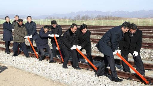 south and north korean government officials connect northern and southern railroad tracks during a groundbreaking ceremony