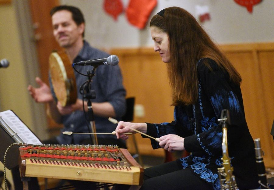 Eve Lawler, right, plays a hammered dulcimer for roughly 60 children and adults Thursday during the Music Around the Mediterranean program at the Ela Area Public Library in Lake Zurich.