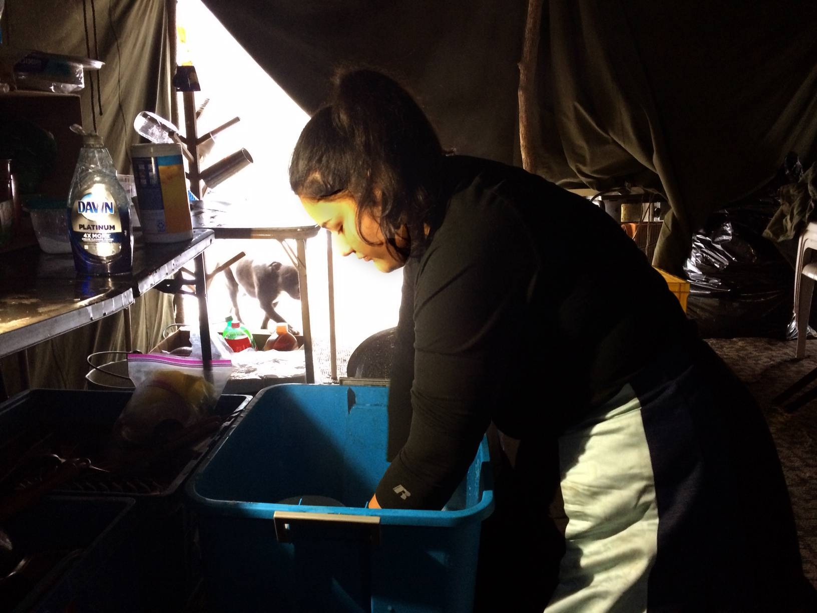 Sarah Shomin, who grew up on a reservation in Michigan, washes dishes in the camp's kitchen tent.