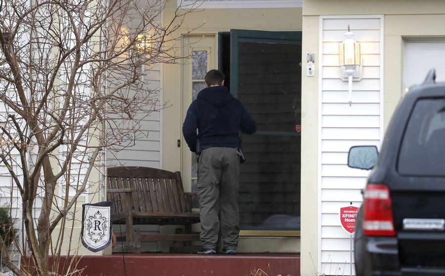 "A police officer enters the Round Lake-area home of a 47-year-old woman who was found dead early Monday morning with what authorities are calling ""suspicious injuries."" A 52-year-old man who lives in the home is in custody."