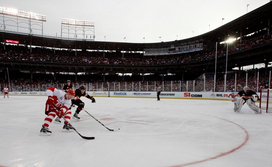 Detroit Red Wings' Dan Cleary, left, moves the puck as Chicago Blackhawks' Cameron Barker defends during the third period of the NHL Winter Classic hockey game at Wrigley Field. The Red Wings won 6-4.