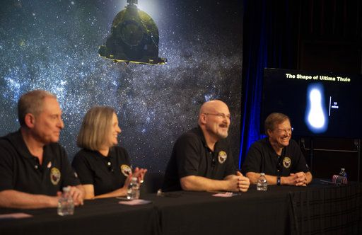 A new image of Ultima Thule, right, is displayed during a press conference after the New Horizons team received confirmation from the spacecraft has completed a flyby of Ultima Thule, Tuesday, Jan. 1, 2019, at the APL in Laurel, Md. The spacecraft survived the most distant exploration of another world, a tiny, icy object 4 billion miles away that looks to be shaped like a peanut or bowling  pin. From left are, New Horizons principal investigator Alan Stern, mission operations manager Alice Bowman, mission systems engineer Chris Hersman, and project scientist Hal Weaver. (Joel Kowsky/NASA via AP)