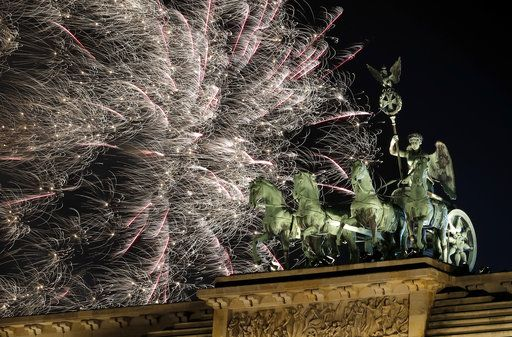 Fireworks light the sky above the Quadriga at the Brandenburg Gate shortly after midnight in Berlin, Germany, Tuesday, Jan. 1, 2019. Hundred thousands of people celebrated New Year's Eve welcoming the new year 2019 in Germany's capital.