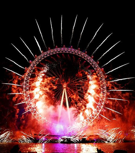 Fireworks explode over the London Eye during the New Year's eve celebrations after midnight in London, Tuesday, Jan. 1, 2019.
