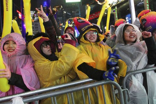 Ting Ouyang, from Philadelphia, Pa., right, and others take part in the New Year's Eve festivities in New York's Times Square, Monday, Dec. 31, 2018.