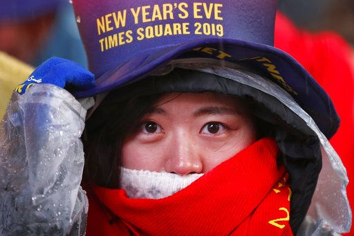 A reveler adjusts her hat as she waits in Times Square in New York on Monday, Dec. 31, 2018, while taking part in a New Year's Eve celebration.