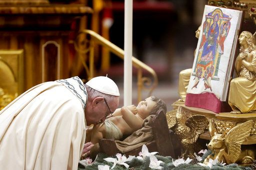 Pope Francis kisses a statue of Baby Jesus as he celebrates a new year's eve vespers Mass in St. Peter's Basilica at the Vatican, Monday, Dec. 31, 2018.