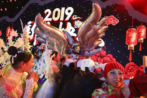 Performers take selfies at the end of a countdown to the new year event in Beijing, China, Tuesday, Jan. 1, 2019.