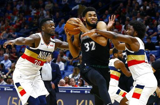 Minnesota Timberwolves center Karl-Anthony Towns (32) drives to the basket as New Orleans Pelicans forwards Julius Randle (30) and Solomon Hill (44) defend during the first half of an NBA basketball game, Monday, Dec. 31, 2018, in New Orleans.
