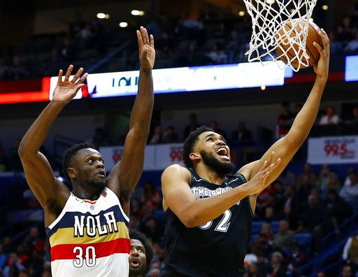 Minnesota Timberwolves center Karl-Anthony Towns (32) makes a basket as New Orleans Pelicans forward Julius Randle (30) tries to defend during the first half of an NBA basketball game, Monday, Dec. 31, 2018, in New Orleans.