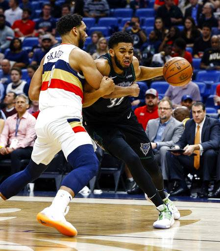 Minnesota Timberwolves center Karl-Anthony Towns (32) is fouled by New Orleans Pelicans center Jahlil Okafor (8) as he drives to the basket during the first half of an NBA basketball game, Monday, Dec. 31, 2018, in New Orleans.