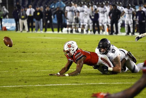Utah quarterback Jason Shelley (15) fumbles as he is tackled by Northwestern defensive lineman Joe Gaziano (97) as he runs during the second half of the Holiday Bowl NCAA college football game Monday, Dec. 31, 2018, in San Diego. The fumble was picked up by Northwestern and returned for an 86-yard touchdown.