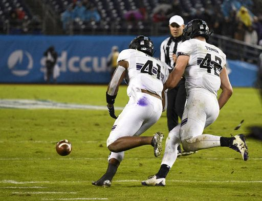 Northwestern safety Jared McGee (41) picks up a fumble next to linebacker Paddy Fisher (42) during the second half of the Holiday Bowl NCAA college football game against Utah Monday, Dec. 31, 2018, in San Diego. McGee returned the fumble for an 86-yard touchdown.