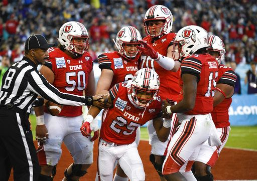 Utah players congratulate wide receiver Jaylen Dixon (25) after scoring a touchdown during the first half of the Holiday Bowl NCAA college football game against Northwestern, Monday, Dec. 31, 2018, in San Diego.