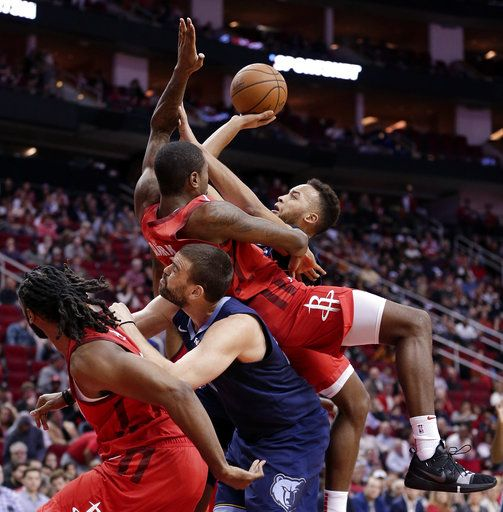 Memphis Grizzlies forward Kyle Anderson, right, shoots as Houston Rockets forward Gary Clark, top, falls onto center Marc Gasol, who pushes off of Houston Rockets center Nene, left, during the first half of an NBA basketball game Monday, Dec. 31, 2018, in Houston.