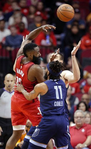 Houston Rockets guard James Harden (13) passes the ball over Memphis Grizzlies guard Mike Conley (11) and center Marc Gasol, back, during the first half of an NBA basketball game Monday, Dec. 31, 2018, in Houston.