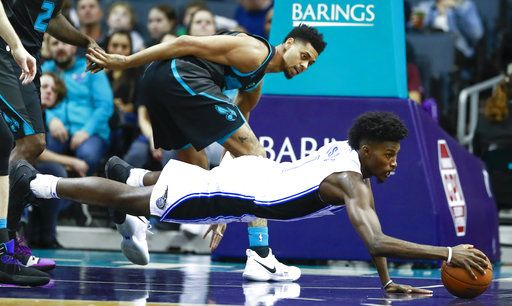 Orlando Magic forward Jonathan Isaac, right, dives for the ball while being covered by Charlotte Hornets guard Jeremy Lamb in the first half of an NBA basketball game Monday, Dec. 31, 2018, in Charlotte, N.C.