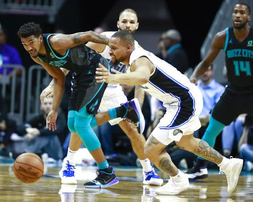 Charlotte Hornets guard Malik Monk, left, and Orlando Magic guard Isaiah Briscoe scramble for the ball in the first half of an NBA basketball game Monday, Dec. 31, 2018, in Charlotte, N.C.