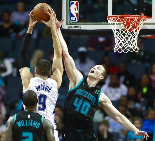 Charlotte Hornets center Cody Zeller, right, tries to block Orlando Magic center Nikola VuCevic from shooting during the second half of an NBA basketball game Monday, Dec. 31, 2018, in Charlotte, N.C. The Hornets won 125-100.