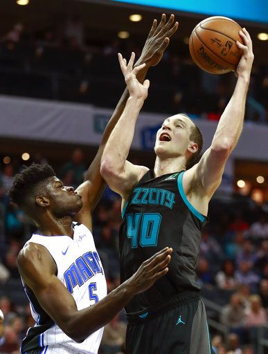 Charlotte Hornets center Cody Zeller (40) goes up a basket while being covered by Orlando Magic center Mo Bamba (5) in the first half of an NBA basketball game Monday, Dec. 31, 2018, in Charlotte, N.C.