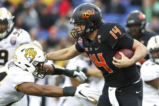 Oklahoma State quarterback Taylor Cornelius tries to stiff-arm Missouri linebacker Terez Hall during the first half of the Liberty Bowl NCAA college football game in Memphis, Tenn., Monday, Dec. 31, 2018. (Joe Rondone/The Commercial Appeal via AP)