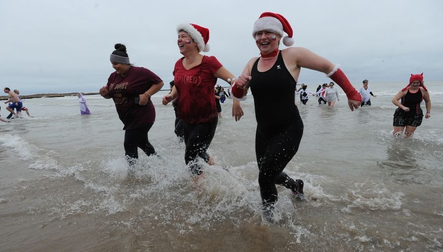 Monika Surovych of Franklin Park and her friends brave the cold water Tuesday during the Polar Bear Plunge in Lake Michigan.