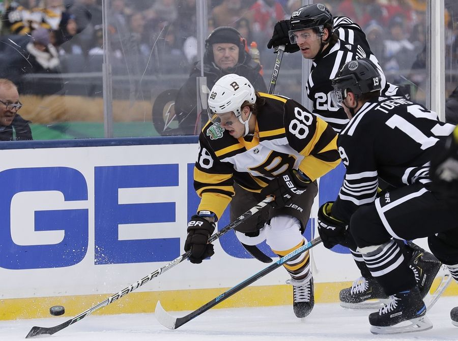 Boston Bruins right wing David Pastrnak (88) controls the puck against Chicago Blackhawks center Jonathan Toews (19) and left wing Brandon Saad (20) in the first period of the NHL Winter Classic hockey game at Notre Dame Stadium, Tuesday, Jan. 1, 2019, in South Bend, Ind.