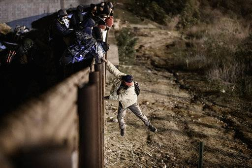 A migrant jumps the border fence to get into the U.S. side to San Diego, Calif., from Tijuana, Mexico, Tuesday, Jan. 1, 2019. Discouraged by the long wait to apply for asylum through official ports of entry, many migrants from recent caravans are choosing to cross the U.S. border wall and hand themselves in to border patrol agents.