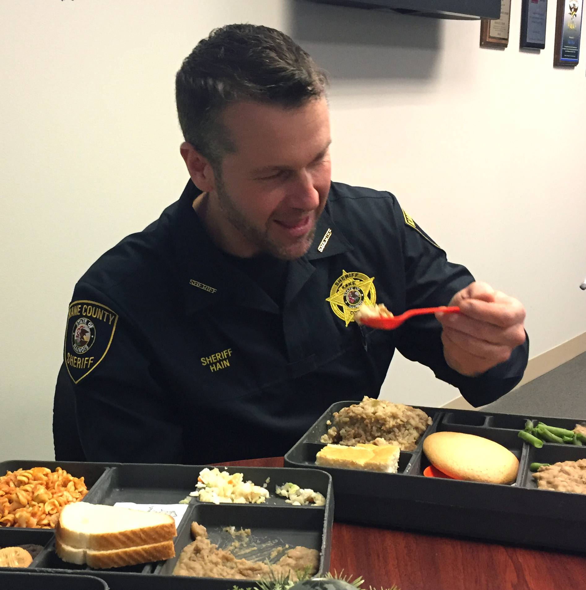 Kane County Sheriff Ron Hain samples lunches served to jail detainees before spending Wednesday night in a cell. He said he wants to determine the validity of complaints from some prisoners about food, clothing and temperatures inside the jail.