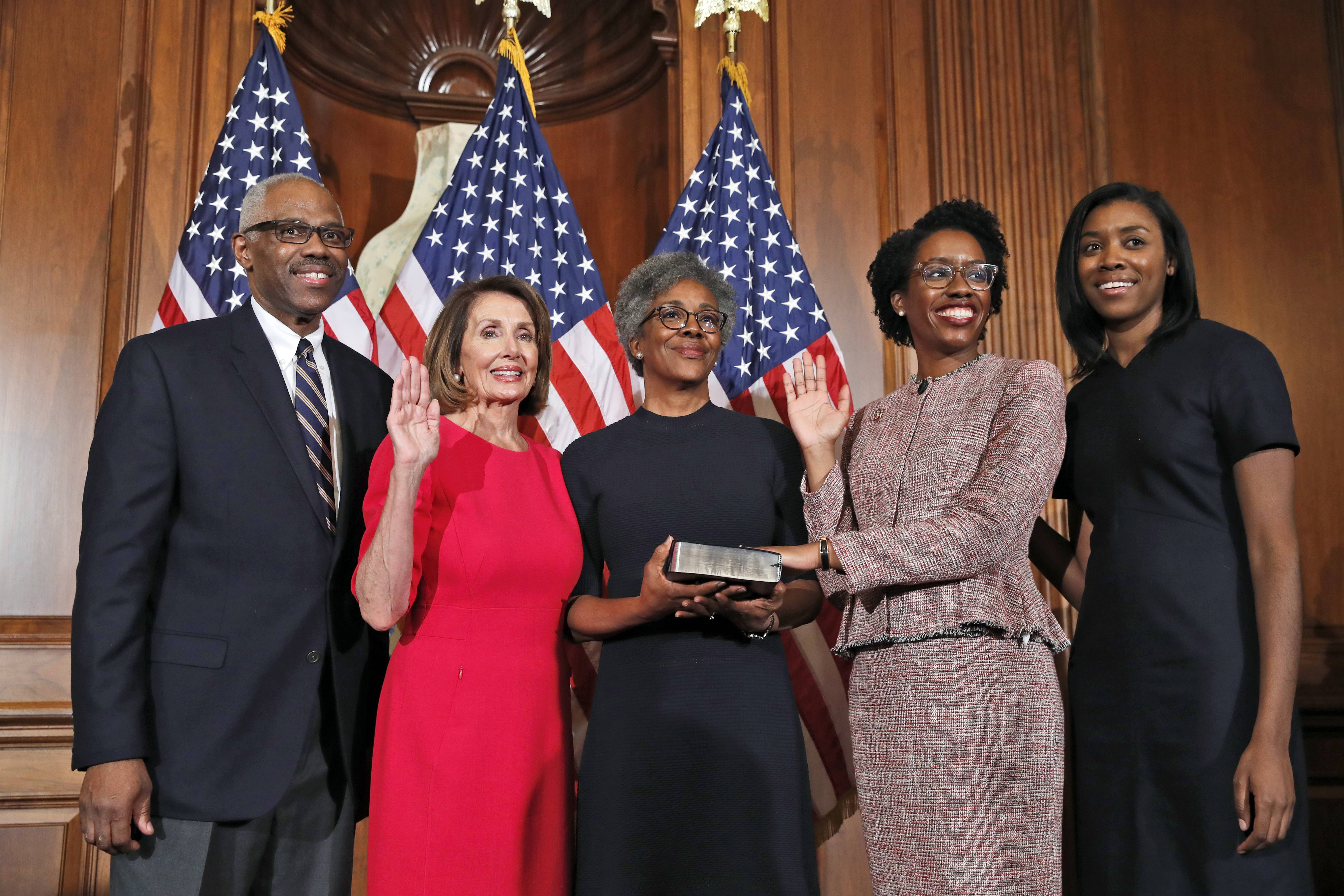 House Speaker Nancy Pelosi of Calif., left, poses during a ceremonial swearing-in with Rep. Lauren Underwood of Naperville, second from right, and her family on Capitol Hill Thursday in Washington during the opening session of the 116th Congress.