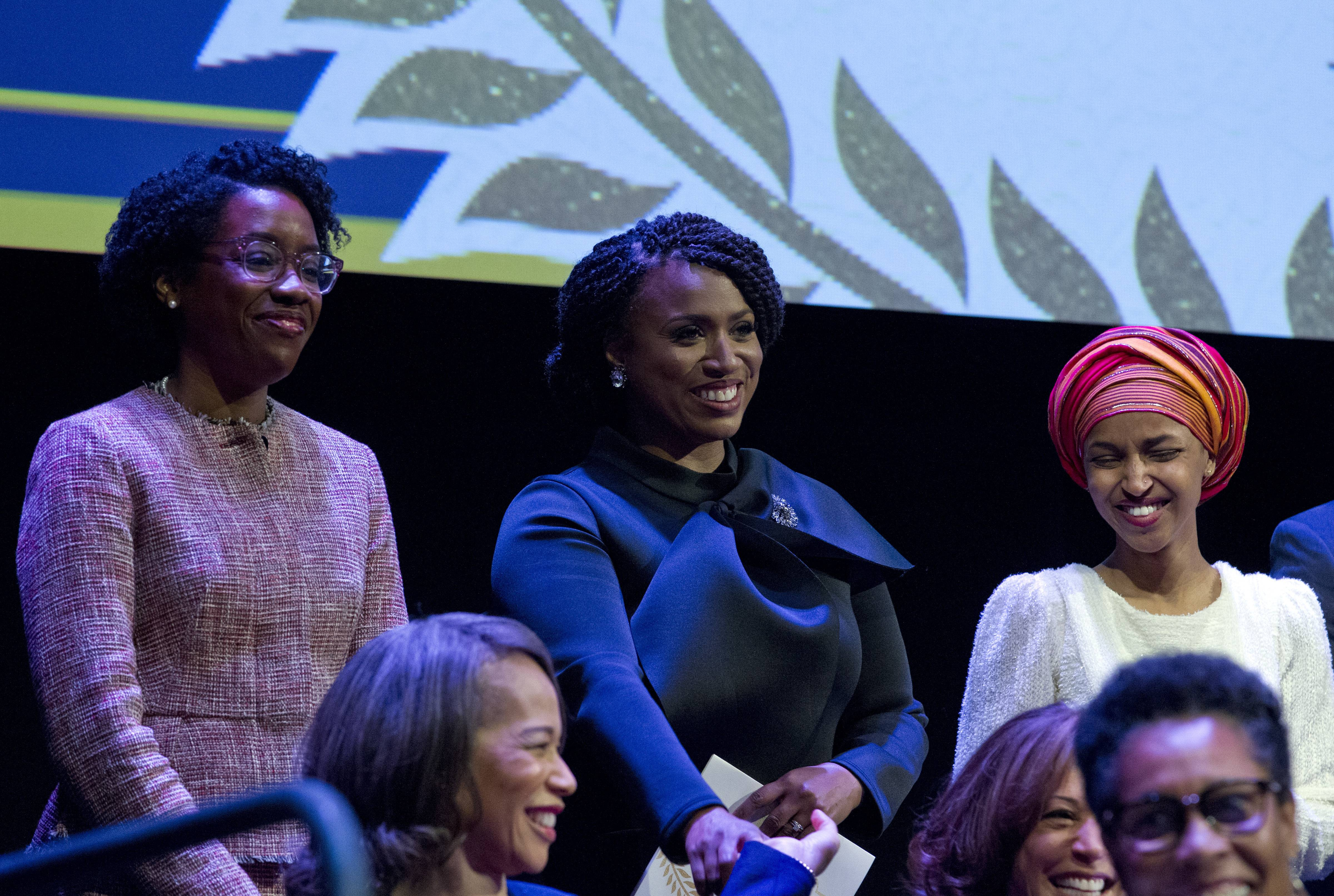 From left, Lauren Underwood, a Naperville Democrat; Ayanna Pressley, a Massachusetts Democrat; and Ilhan Omar, a Minnesota Democrat, gather Thursday during the swearing-in ceremony of Congressional Black Caucus members at The Warner Theatre in Washington.