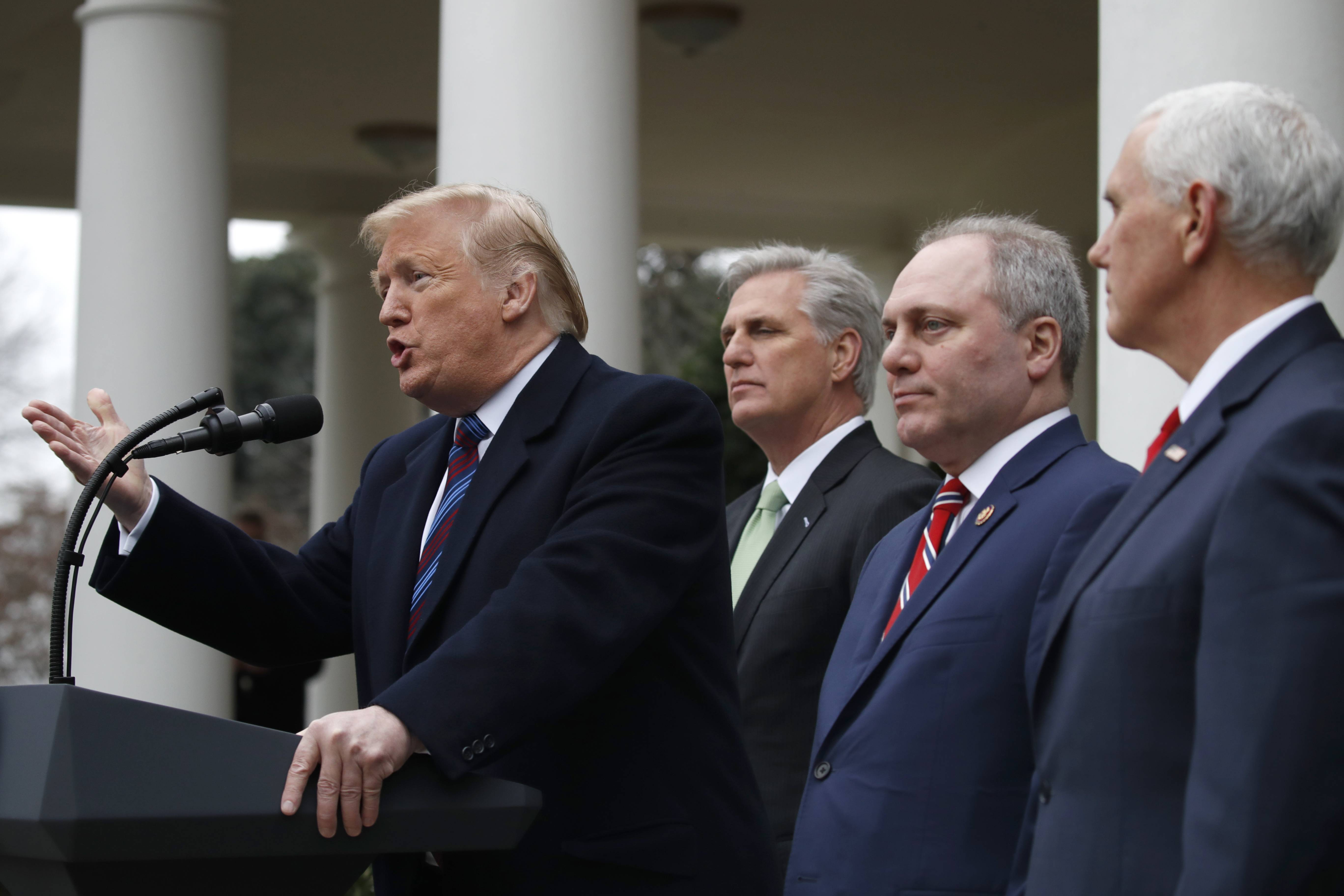 President Donald Trump speaks Friday in the Rose Garden of the White House after a meeting with Congressional leaders on border security, as House Republican leader Kevin McCarthy, House Republican whip Steve Scalise and Vice President Mike Pence listen.