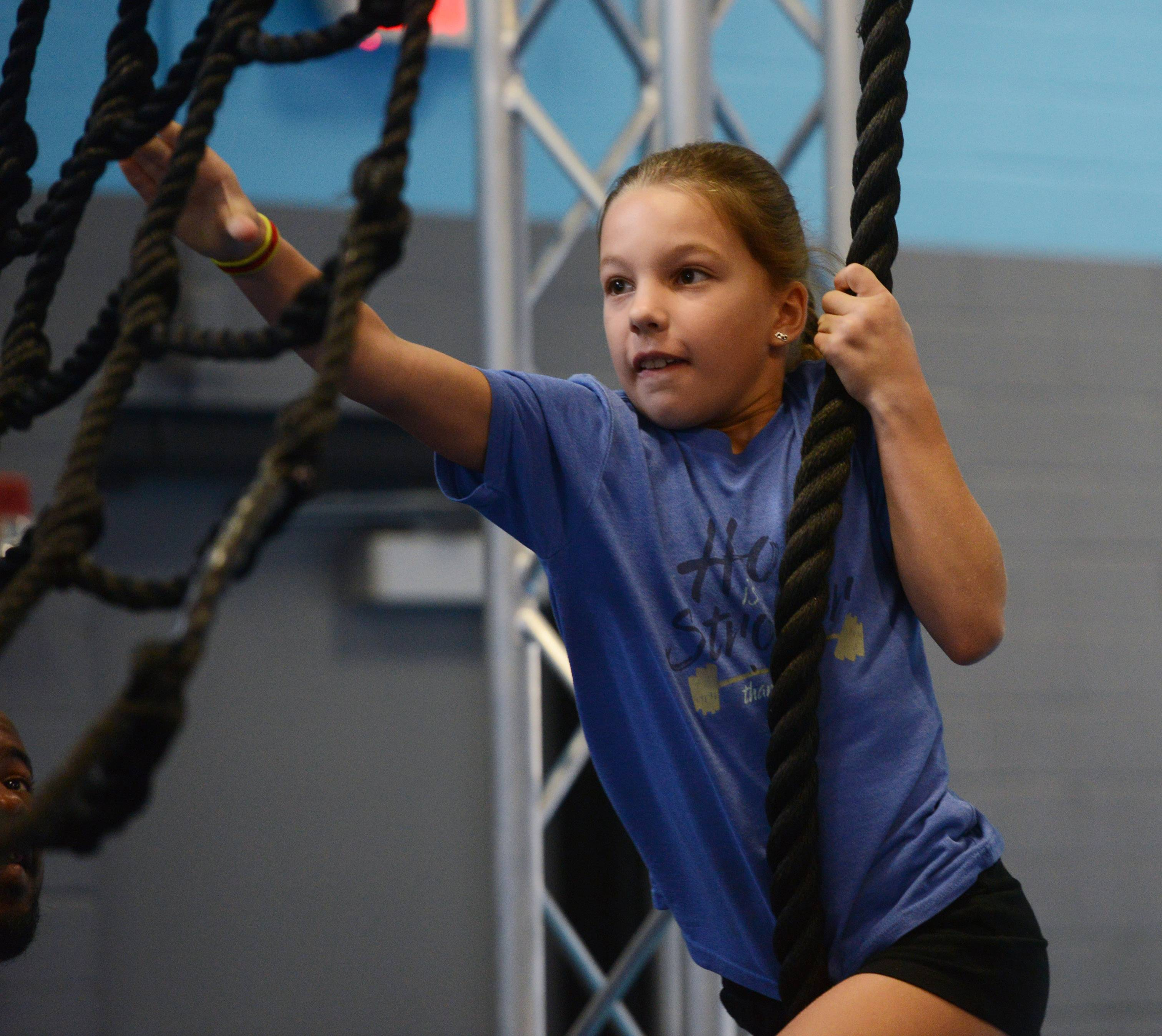Elsie Phipps, 9, swings from a rope to a net at the Windy City Ninjas gym in Elmhurst. Owner Tom Rhomberg says the gym is a perfect spot for kids to put away their electronic devices and get excited about physical fitness.