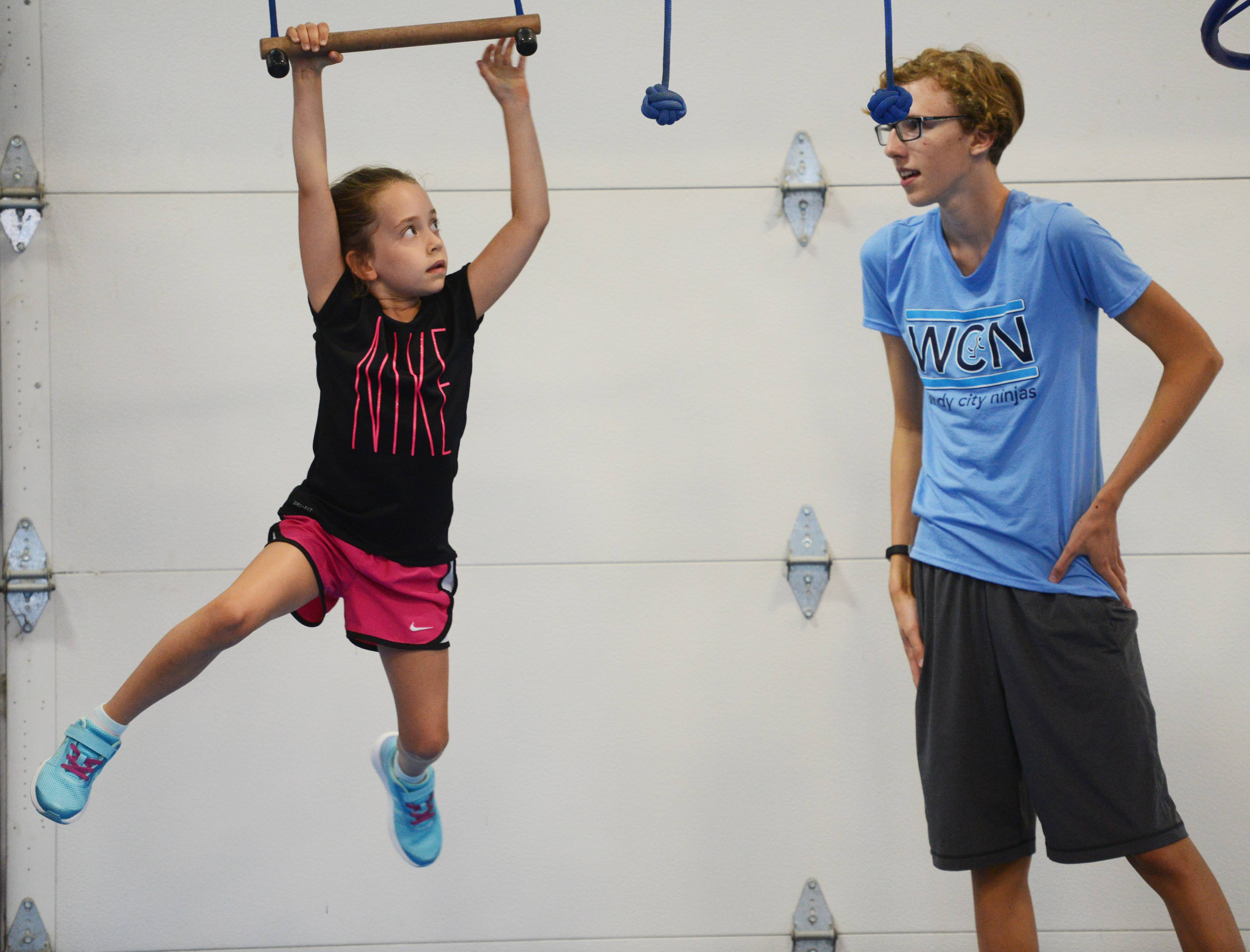 Harper Staley, 6, navigates an obstacle under the guidance of coach Evan Sedlacek.